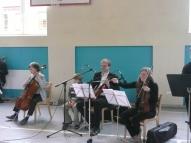 Blakus muzicē skolēni un skolotāji